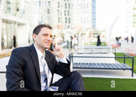 Handsome, attractive young businessman sitting on bench, using talking holding smartphone phone mobile cellphone smiling in suit and tie, cheerful on  - Stock Photo
