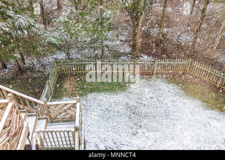 Closeup of empty wooden deck of house with staircase, steps, stairs, trees, forest, lawn grass in backyard in neighborhood with snow covered ground du - Stock Photo