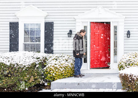 Young man outside front yard red door of house with snow during blizzard white storm, snowflakes falling letting calico cat outside outdoors to porch - Stock Photo