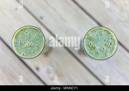 Macro closeup of two green vegetable fruit smoothies pair couple in glasses outside outdoors on wooden deck background for healthy raw vegan breakfast - Stock Photo