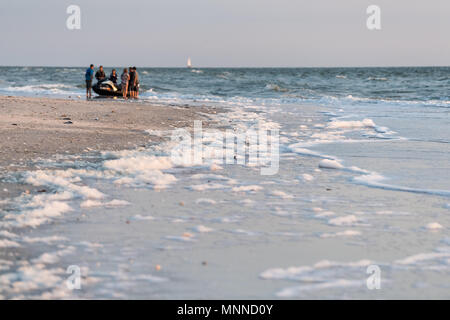 Naples, USA - April 29, 2018: Closeup of lots of foam on coast during red tide algae bloom toxic beach in Florida Gulf of Mexico during sunset on sand - Stock Photo