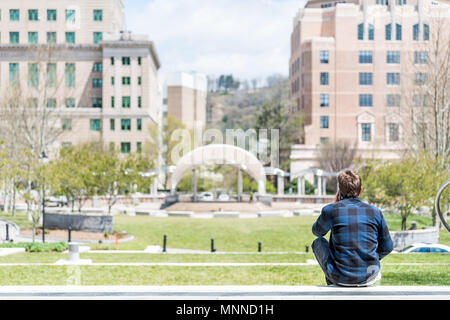 Asheville, USA - April 19, 2018: Back of young hipster millennial man sitting looking at buildings, courthouse and green Pack Square Park in hippie No - Stock Photo