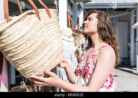Closeup of young woman shopping for straw beach bag in outdoor market shop store in European, Greece, Italy, Mediterranean town, village in colorful s - Stock Photo