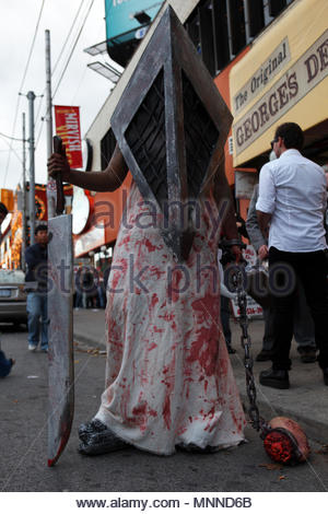 A street performer dressed as Pyramid-Head from the Silent Hill video game series poses on a street corner near Halloween. - Stock Photo