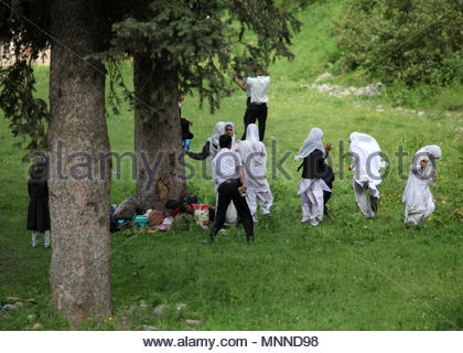 Muslim school children dressed in school uniforms chase each other during a school outing. This is one of the few times boys and girls can mingle. - Stock Photo