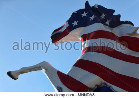 A statue of a horse painted in the stars and Stripes located in front of The New York Mounted Police Unit Headquarters as a memorial for those killed  - Stock Photo