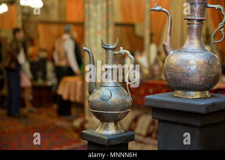 Old vintage copper hooded jug . Old copper water ewer over yellow background - Stock Photo