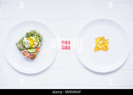 Concept of choice and equality - healthy food or medical pills, top view on the white plates and wooden table. Choice between natural and synthetic way of health care. Alternative medicine. - Stock Photo