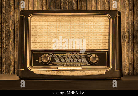 Old radio on a table. Front view. Matchboards on background. - Stock Photo