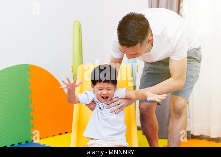 Asian father accompanying child on the playground slider at home. Happy family with toys - Stock Photo