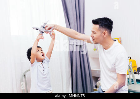 Curious kid looking at the plane toy and playing with father. Asian family playing toys together at home - Stock Photo