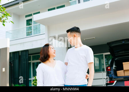 Asian couple standing in front of their new house. Newlyweds family just moved in new home and car carrying boxes - Stock Photo