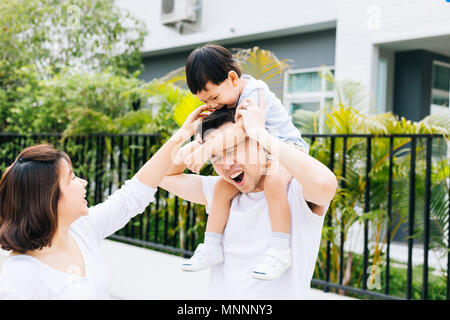 Cute Asian father piggybacking his son along with his wife in the park. Excited family spending time together with happiness - Stock Photo
