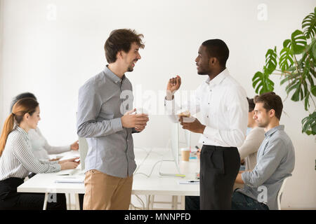 Friendly multiracial colleagues chatting together in office duri - Stock Photo