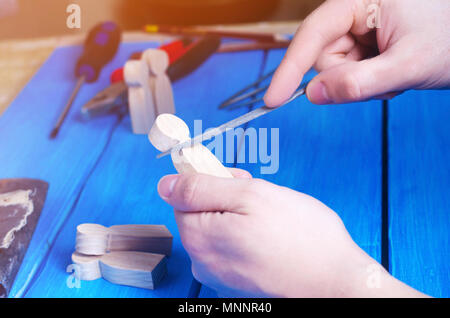 Men's hands make a hand-made article of wood on the background of a blue table with tools. Work at home and in the workshop. Wooden figures of people. - Stock Photo
