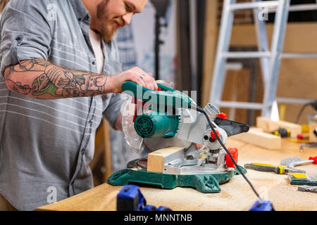 circular saw for cutting boards into the hands of the builder, the man sawed bars, construction and home renovation, repair and construction tool - Stock Photo