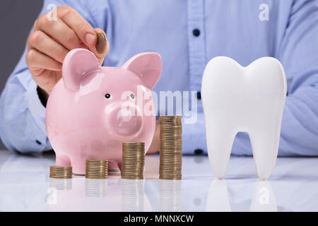 Man Inserting Coin In Piggy Back For Oral Dental Treatment - Stock Photo