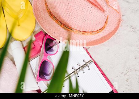 Colorful summer beachwear, flip flops, towel, hat, sunglasses and book on sand beach.