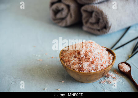Wooden bowl with pink salt on neutral background - Stock Photo