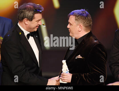 18 May 2018, Germany, Munich: Premier of Bavaria Markus Soeder (CSU, l) shakes hands with actor Hape Kerkeling while Kerkeling holds a 'Blue Panther' trophy at the Bayerischer Fernsehpreis (Bavarian Television Awards) at the Prinzregententheater. Kerkeling received the 'Ehrenpreis' award. Photo: Tobias Hase/dpa - Stock Photo