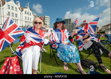 People wave Union Jack flags and celebrate Prince Harry and Meghan Markle's wedding at a Royal wedding event on the seafront at Bexhill On Sea, East Sussex, UK, England. - Stock Photo