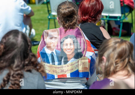 A person with a flag with the faces of Prince Harry and Meghan Markle on it at a Royal wedding event in Bexhill On Sea, East Sussex, England. - Stock Photo