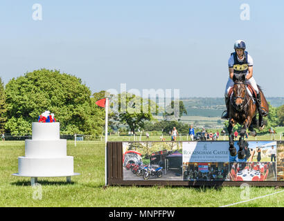 Corby, UK. 19th May 2018. The horse Ete Rose and rider Arthur Dufurt leap the 'Royal Wedding fence' (decorated to celebrate the wedding that day of Prince Harry and Meghan Markle) in the cross country event during the international horse trials at the park of Rockingham Castle, Corby, England on 19 May 2018. Credit: Michael Foley/Alamy Live News - Stock Photo