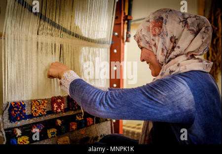 A woman in traditional dress sits weaving carpets in Tazenakht, southern Morocco, Africa - Stock Photo