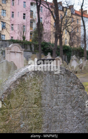 Detail of the structure of an old tombstone with a stones brought there. Colorful houses in the background. Jewish cemetry in Zizkov, Prague, Czech re - Stock Photo