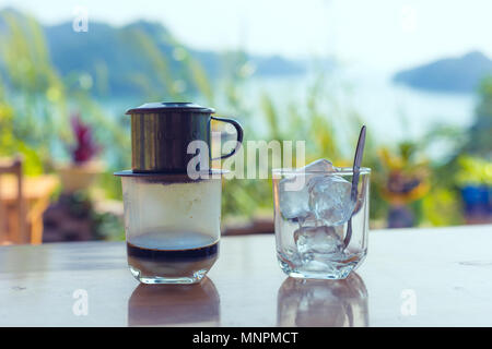 traditional Vietnam coffee with landscape of Halong bay in background - Stock Photo