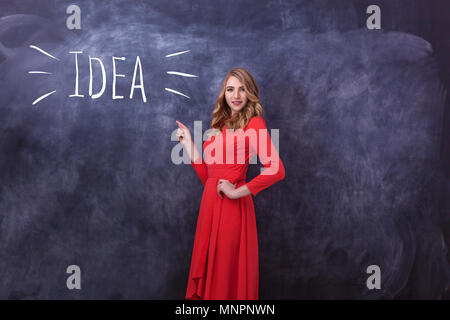 Young beautiful girl in red dress shows a hand on drawing. On a black board the word idea is written and the girl shows on them a hand. Various human  - Stock Photo