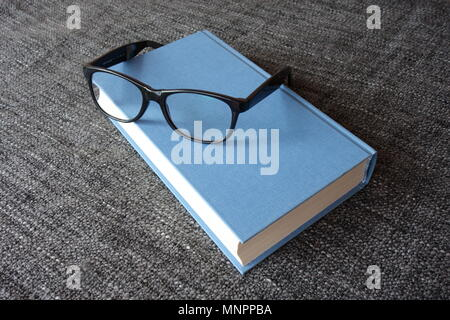 Blue hardcover and a pair of reading glasses - Stock Photo