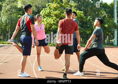 four asian young adults warming up stretching legs on track. - Stock Photo