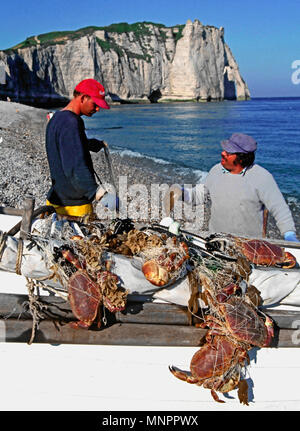 FISHERMEN WITH THEIR CATCH OF SHELLFISH. ETRETAT. NORMANDY. FRANCE. JUNE 2014. The iconic cliffs and the Arch Porte d'aval with the local fishermen an - Stock Photo
