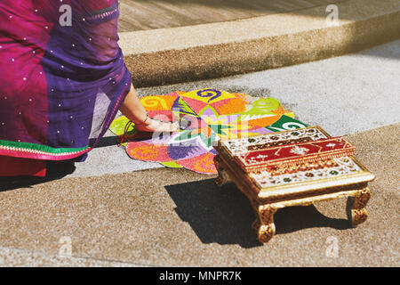 Women coloring tradition colorful rice art or sand art (Rangoli) on the floor with paper pattern using dry rice and dry flour with colored from natura - Stock Photo