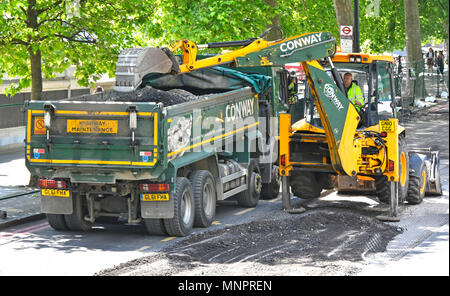 London street scene hydraulic excavator digger machine & driver scrape tarmac road works loading tipper lorry for cycle lane on Embankment England UK - Stock Photo