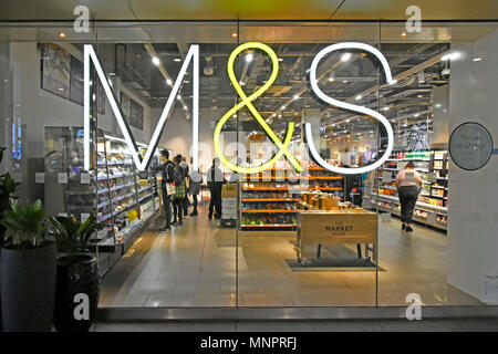 M&S foodhall illuminated sign on shop window & interior of Marks and Spencer food hall at Westfield Shopping Centre Stratford East London England UK - Stock Photo