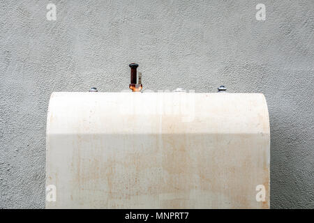 old weathered oil taink against a white stucco wall - Stock Photo