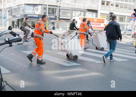 garbage collectors crossing street in antwerp, belgium - Stock Photo