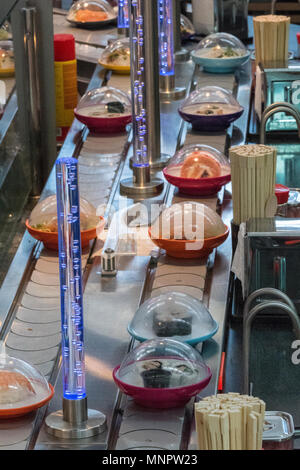 The high street food retailer and fast food restaurant and takeaway you sushi. Sushi and Japanese foods going around on carousel for customers choose. - Stock Photo
