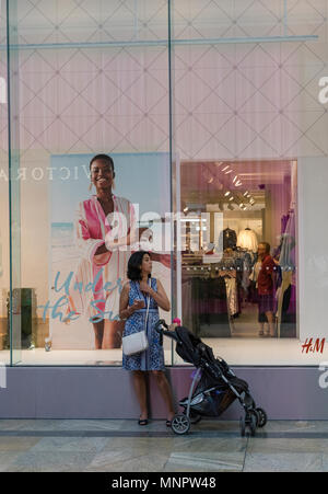 A young woman with a baby in a pushchair standing outside of a women's clothes shop in a shopping centre looking at a mobile phone or portable device. - Stock Photo