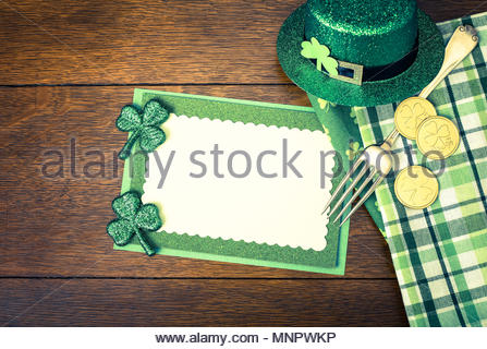 Happy St. Patricks Day Menu or Invite Card with Shamrocks, Hat, Lucky Coins, Napkins and fork from top down view with blank room or space for copy, te - Stock Photo