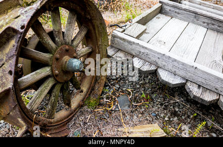 Vintage antique automotive tractor wheel covered in rust next to a fallen fence - Stock Photo