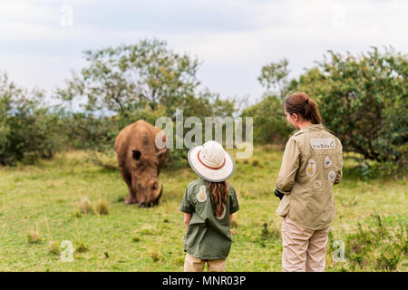 Back view of family on safari walking close to  white rhino - Stock Photo