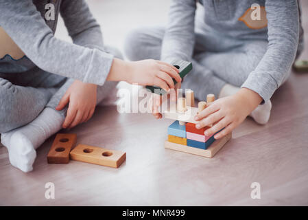 Children play with a toy designer on the floor of the children's room. Two kids playing with colorful blocks. Kindergarten educational games - Stock Photo