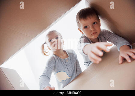 Two a little kids boy and girl opening cardboard box and looking inside with surprise - Stock Photo