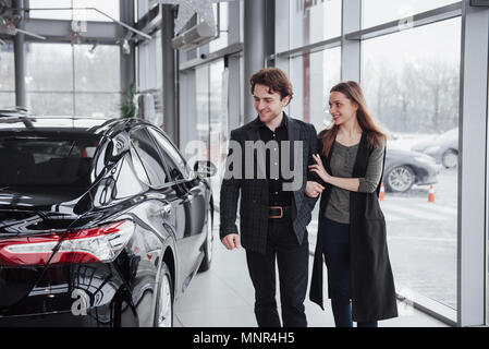 Proud owners. Beautiful young happy couple hugging standing near their newly bought car smiling joyfully showing car keys to the camera copyspace family love relationship lifestyle buying consumerism - Stock Photo