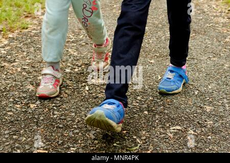 Two pairs of children's legs walking on asphalt, Jourama Falls, Bruce Hwy, Yuruga QLD, Australia - Stock Photo