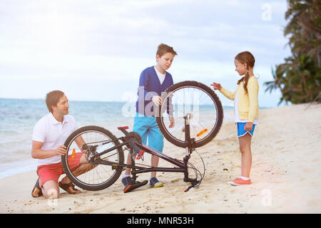 Family of teenage boy, little girl and father repairing bicycle outdoors on tropical beach at summer - Stock Photo
