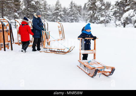 Beautiful family of father and kids enjoying snowy winter day outdoors having fun sledging - Stock Photo